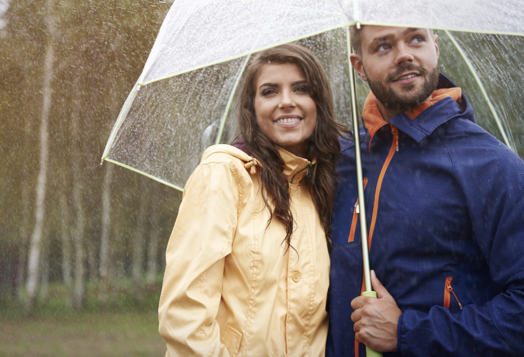 Representación visual de la tranquilidad de una pareja bajo un paraguas porque su casa está segura con domótica